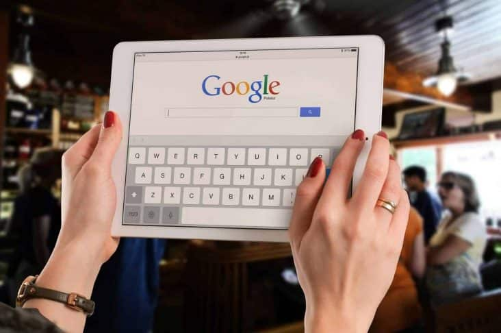 A woman holding an Apple tablet making a search on Google for digital marketing services